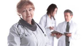 Adult female doctor therapist on blurred background of colleagues stock image