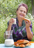 The adult female eats house pies with fresh milk Royalty Free Stock Photography