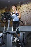 Adult female on elliptical machine. Royalty Free Stock Images