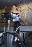 Adult female on elliptical machine. royalty free stock images
