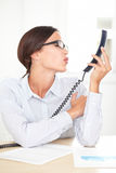 Adult female executive kissing to the phone Royalty Free Stock Photography