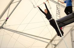 An adult female hangs on a flying trapeze at an indoor gym. The woman is an amateur trapeze artist.  royalty free stock photography