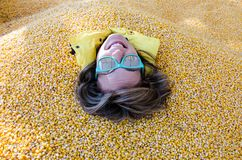 An adult female has her entire body covered and buried in corn kernels stock image