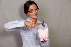 Adult female holding and breaking money box Royalty Free Stock Images