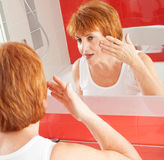 Adult female looking at mirror Stock Photos