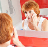 Adult female looking at wrinkles in mirror Stock Images