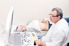 Adult female patient going through abdomen ultrasound at private clinic. Royalty Free Stock Images
