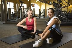 Adult female with personal trainer at gym. Stock Photos