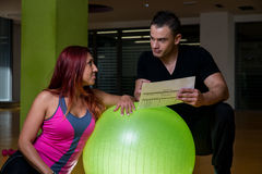 Adult female with personal trainer at gym Stock Photography