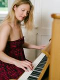 Adult female playing the piano Stock Photo