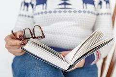 Adult female reading book with glasses in hand Royalty Free Stock Image
