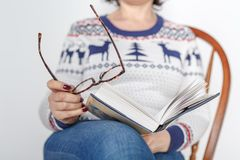 Adult female reading book with glasses in hand Royalty Free Stock Photo
