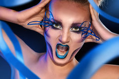 Adult female screaming on camera with creative make up face. In studio Stock Photography