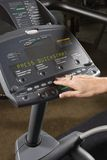 Adult female setting up elliptical machine. Stock Photo