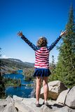 An adult female stands at the top of Twin Lakes overlook in Mammoth Lakes, California, wearing patriotic USA flag colors on the. Fourth of July royalty free stock photo
