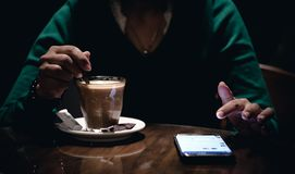 An adult female using her phone and drinking coffee in a dark room stock images