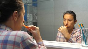 Female cleaning her teeth at home. Adult female washing her teeth with toothpaste in front of mirror in the morning. Morning routine in bathroom and healthy stock video