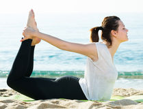 Adult female in white T-shirt is practicing asana Stock Photos