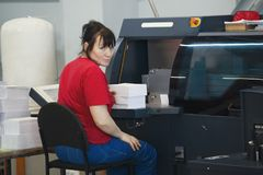 Adult female worker with a stacks of paper in front of print press equipment. Horizontal stock images