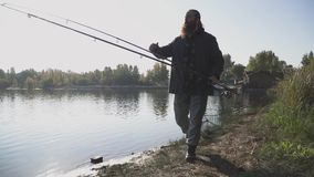 Adult fisherman with long beard walks near the river with fishing rods and fish net. The man looks into the distance. Covering his eyes with his hand from the stock footage