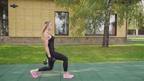 Adult fitness woman doing walking lunges with dumbbells on a sports ground stock video footage