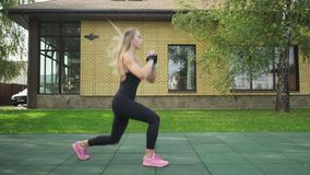 Adult fitness woman makes lunges with a jump on a sports ground stock video
