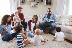 Adult friends entertaining their toddlers in sitting room royalty free stock photos