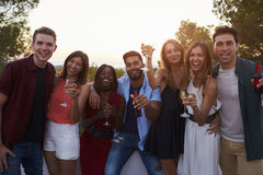 Adult friends at a party on a rooftop looking to camera Royalty Free Stock Photography