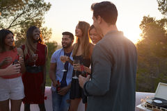 Adult friends at a party on a rooftop at sunset, close up Stock Image