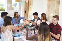 Adult friends serving each other at a patio dinner party Royalty Free Stock Images