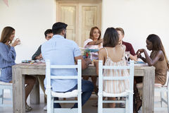 Adult friends sitting together at a dinner party on a patio Stock Photo