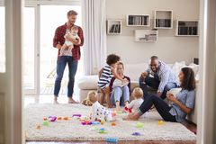 Adult friends with toddlers socialising in sitting room royalty free stock photography