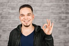Adult funny guy dressed in hoody smiles and show sign ok on brick wall background. Adult funny guy dressed in hoody smiles and show sign ok on a brick wall stock image