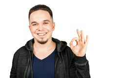 Adult funny guy dressed in hoody smiles and show sign ok. Isolated on white background. Adult funny guy dressed in hoody smiles and show sign ok. Isolated on a stock photos