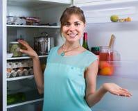 Adult girl arranging space of fridge shelves indoors Stock Image