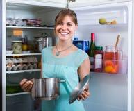 Adult girl arranging space of fridge shelves indoors Stock Photos