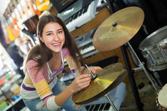 Adult girl choosing drums and accessories Stock Photos
