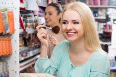 Adult girl choosing face powder Royalty Free Stock Photos