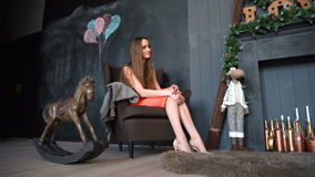 Adult girl in dress sitting in armchair in cozy room, together with the rocking-horse stock video footage