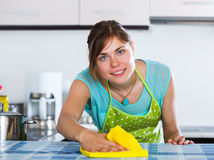 Adult girl dusting surfaces in kitchen Stock Image