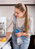 Adult girl dusting surfaces in residential kitchen Royalty Free Stock Photo