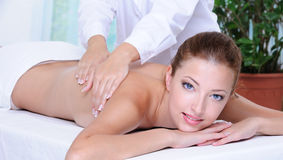 Adult girl getting back massage Stock Photos