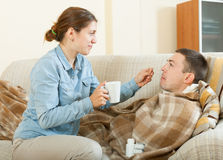 Adult girl giving giving drugs to diseased man Royalty Free Stock Photos