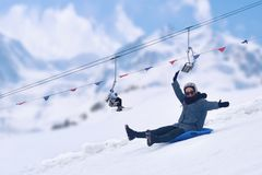 Adult girl having fun. Kites on the sled, laughs, smiles like a child. Winter concept. royalty free stock photography