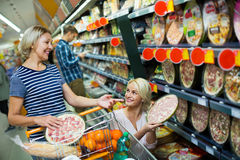 Adult girl helping mother in pizza section Royalty Free Stock Image