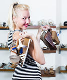 Adult girl holding many pair of shoes. Adult girl holding many pair of heeled shoes in fashion store royalty free stock photography