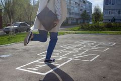 An adult girl passed by the hopscotch and decided to jump royalty free stock images