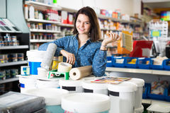 Adult girl is purchasing tools for house improvements. In paint supplies store stock photography