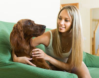 Adult girl with red Irish setter. Smiling adult girl sitting on sofa at home and hugging red Irish setter Royalty Free Stock Image