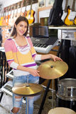 Adult girl selecting drums and accessories Royalty Free Stock Image